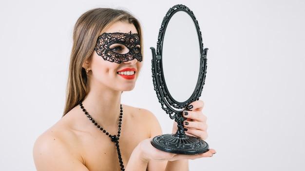 Sourire topless femme en masque de carnaval à la recherche dans le miroir de la main Photo gratuit