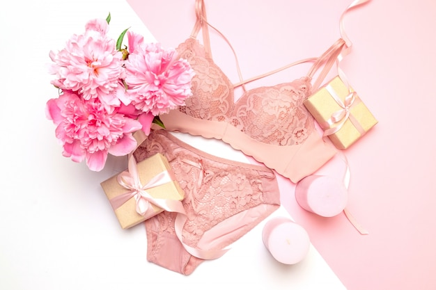 Soutien-gorge et culotte femme en dentelle rose élégante, bougies roses fleurs, un bouquet de belles pivoines, cadeaux Photo Premium