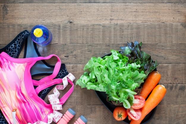 Soutien-gorge de sport de la femme et des aliments sains sur un fond en bois avec fond Photo Premium
