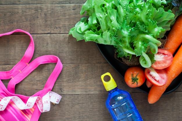 Soutien-gorge de sport de la femme et des aliments sains sur fond en bois Photo Premium