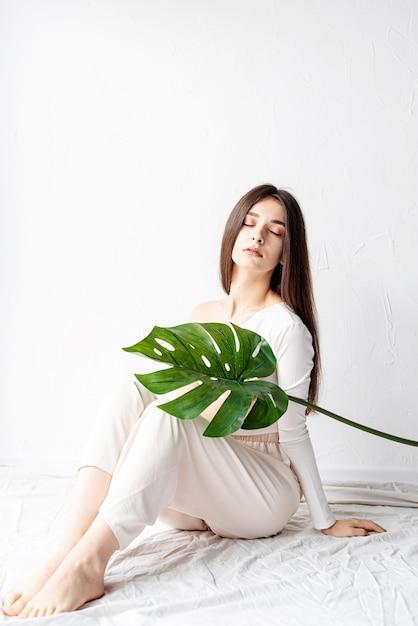 Spa Et Beauté. Soins Personnels Et Soins De La Peau. Heureuse Belle Femme Dans Des Vêtements Confortables Tenant Une Feuille De Monstera Verte Photo Premium