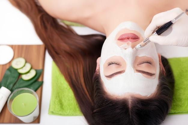 Spa femme appliquant le masque nettoyant pour le visage. soins de beauté. masque à l'argile Photo Premium
