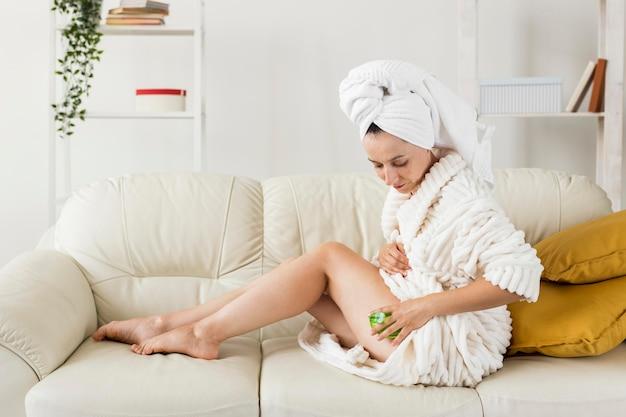 Spa à La Maison Femme Massant Ses Jambes Long Shot Photo gratuit