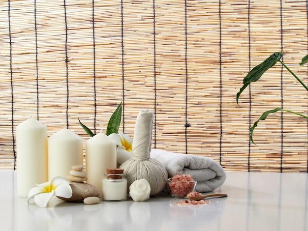 Spa Massage Concept, Boule De Compression Aux Herbes, Crème, Savon De Fleur, Bougie Parfumée Sur Une Table Blanche, Rideau De Bambou Photo Premium