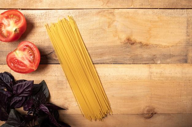 Spaghetti et basilic sur une table en bois. ingrédients pâtes Photo Premium