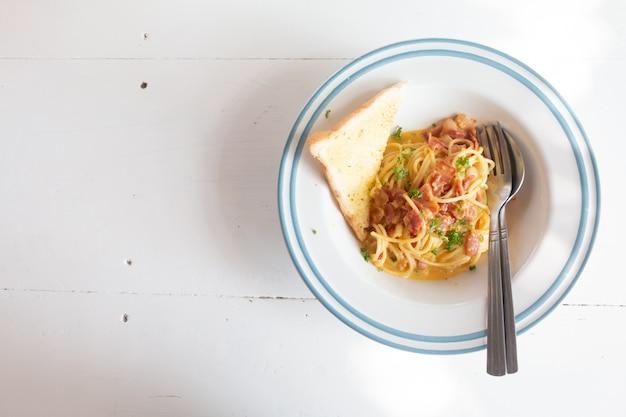 Spaghetti carbonara avec jambon, fromage et pain sur une table blanche Photo Premium