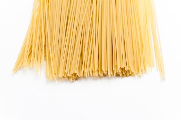 Spaghetti crus sur fond blanc. Photo Premium
