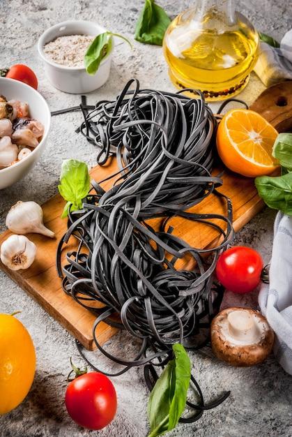 Spaghetti à l'encre de seiche noire non cuite crue avec des ingrédients pour cuisiner le dîner Photo Premium