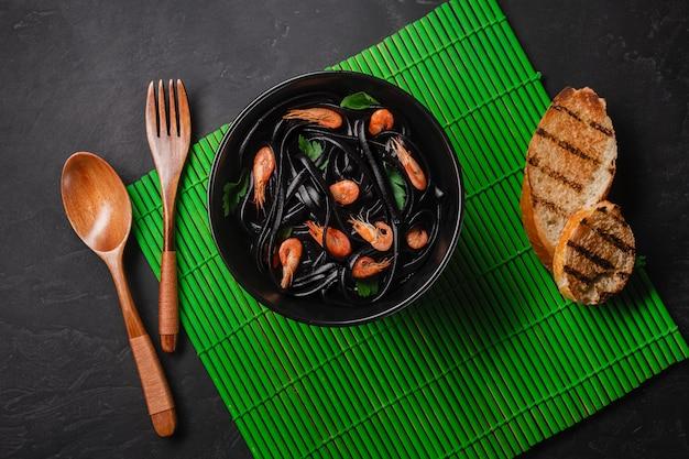 Spaghetti Noir à L'encre De Seiche Et Fruits De Mer. Vue De Dessus Photo Premium