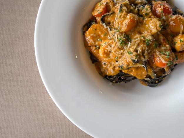 Spaghetti noir à la sauce tomate avec crevettes, tomates saupoudrées d'épices et de fromage Photo Premium