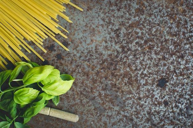 Spaghetti de pâtes au basilic et une cuillère en bois sur un fond métallique rouillé Photo gratuit