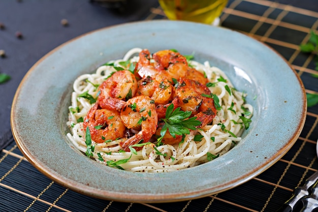 Spaghetti de pâtes aux crevettes, tomates et persil haché. la nourriture saine. repas italien. Photo Premium