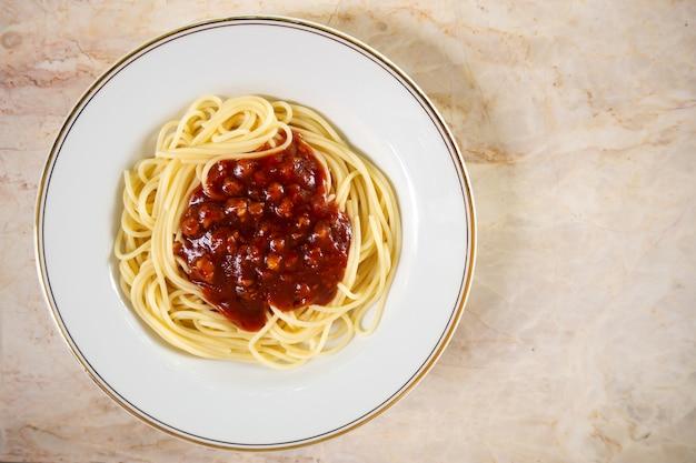 Spaghetti sauce rouge dans une assiette blanche. nourriture italienne. vue de dessus avec espace de copie. Photo Premium