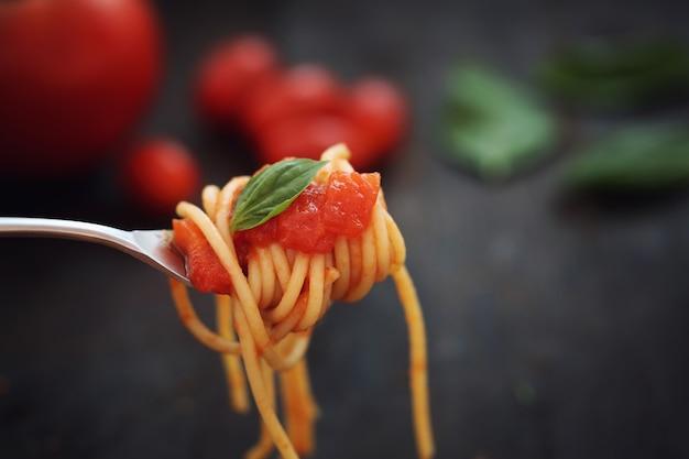 Spaghetti à la sauce tomate et basilic dans un fond en bois foncé Photo Premium