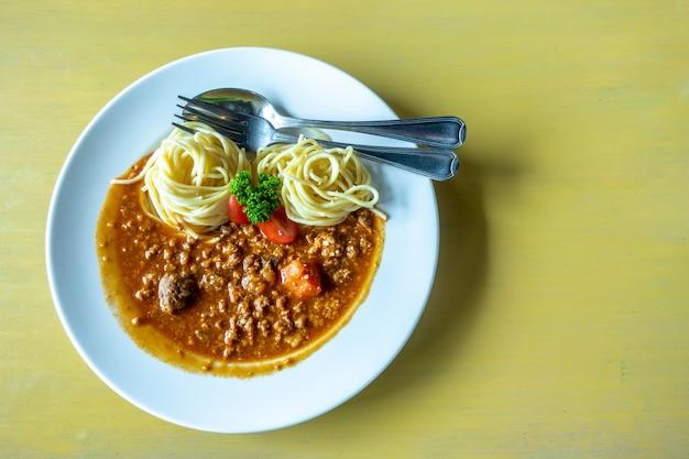Spaghetti à la sauce tomate avec du porc et une fourchette Photo Premium