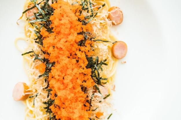 Spaghetti à la saucisse, oeuf de crevette, algues, calmars secs sur le dessus Photo gratuit