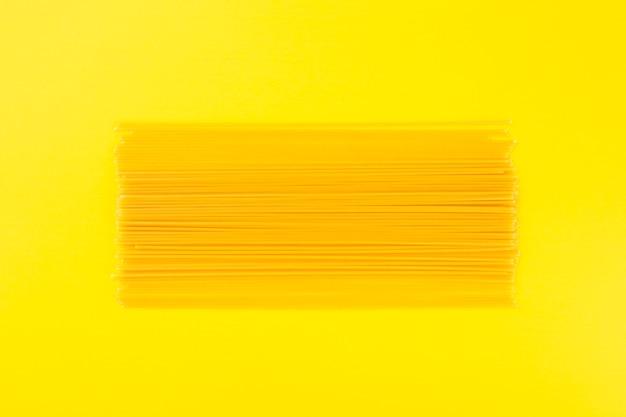 Spaghettis crus sur fond jaune Photo gratuit