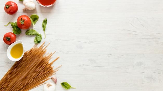 Spaghettis et ingrédients frais sur une table blanche Photo gratuit