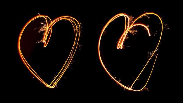 Sparkler light peint en forme de deux coeurs la nuit Photo Premium