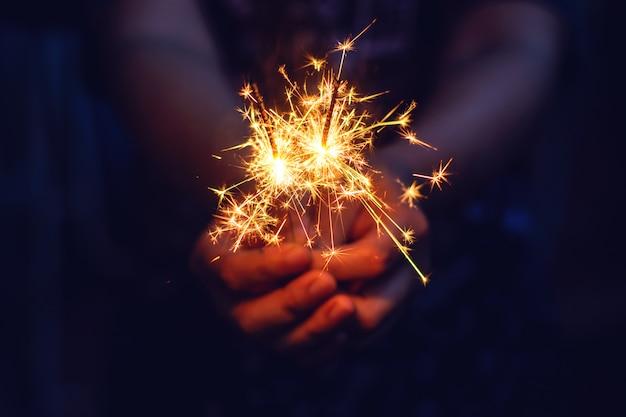Sparkler de nouvel an dans les mains de la femme. Photo Premium