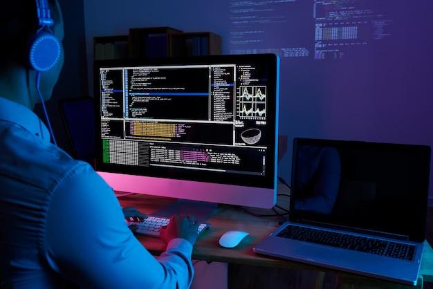 Spécialiste en informatique vérifiant le code à l'ordinateur dans le bureau sombre la nuit Photo gratuit