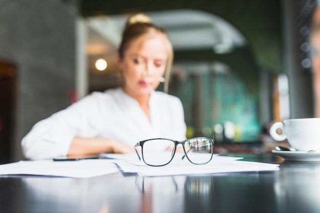 Spectacles et documents devant une femme d'affaires assise dans un café Photo gratuit