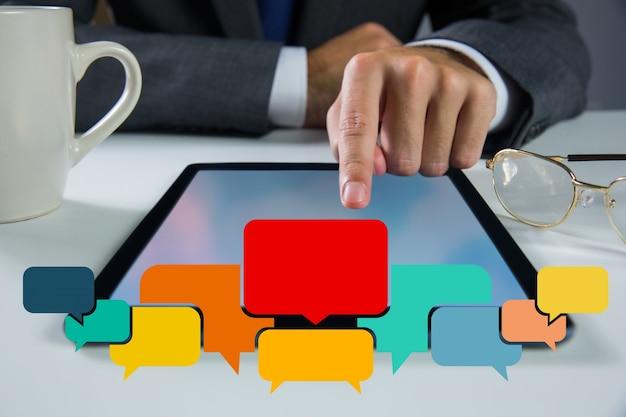 Speech bubbles avec homme d'affaires travaillant sur sa tablette Photo gratuit