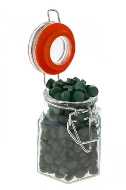 Spiruline aux algues. pilules de spiruline dans un bocal en verre transparent isolé sur fond blanc. concept de super nourriture. algues en comprimés. Photo Premium