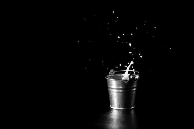 Splash dans un seau en métal avec du lait sur fond noir Photo Premium