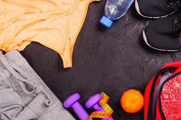 Sport ou fitness sertie de vêtements féminins, haltères, sac et chaussures de sport sur fond noir Photo Premium