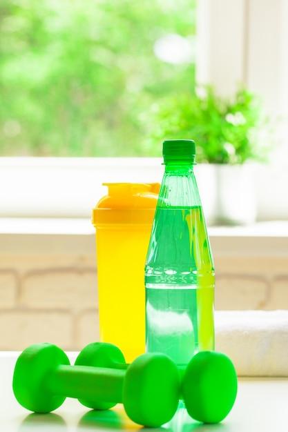 Sport, mode de vie sain et concept d'objets - gros plan d'haltères, bouteille d'eau Photo Premium