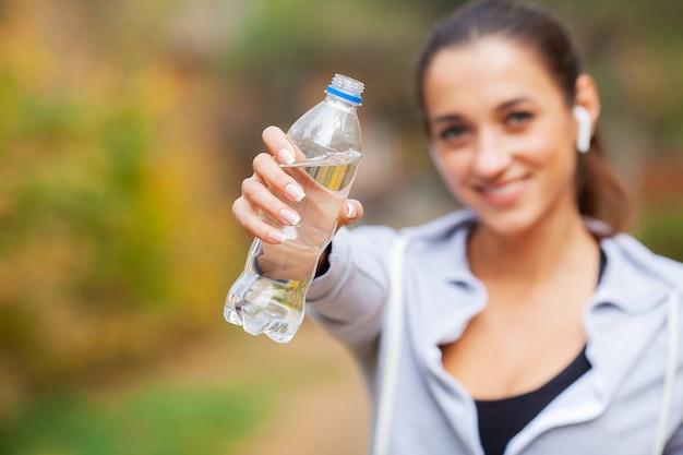 Sport en plein air. femme buvant de l'eau après avoir couru Photo Premium