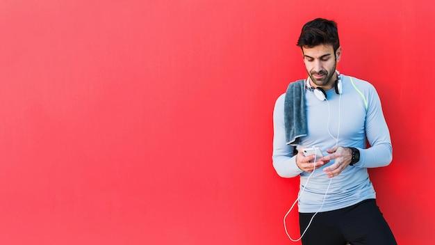 Sportif à l'aide de smartphone sur fond rouge Photo gratuit