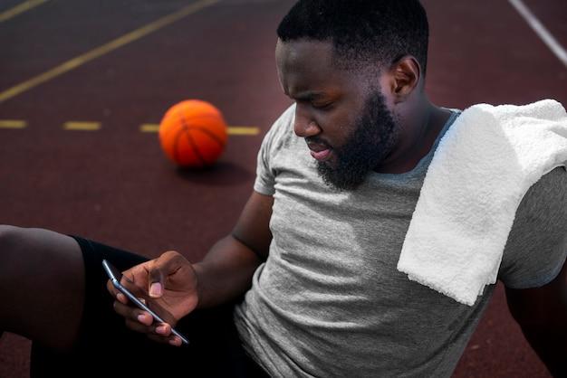 Sportif américain regardant le téléphone Photo gratuit