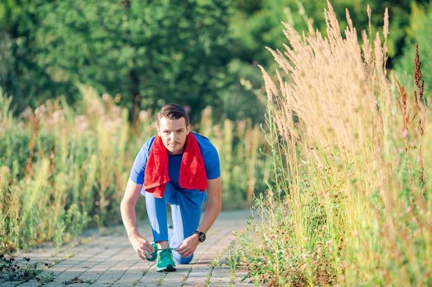 Sportif jeune homme faisant des exercices de sport en plein air dans le parc Photo Premium