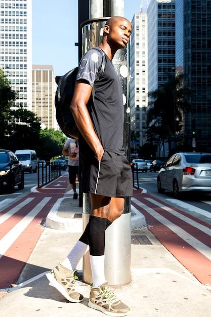 Sportif jeune homme avec sac à dos se penchant sur la route avec les mains dans la poche Photo gratuit