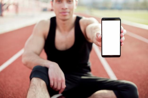 Sportif masculin assis sur la piste de course montrant l'écran du téléphone mobile Photo gratuit