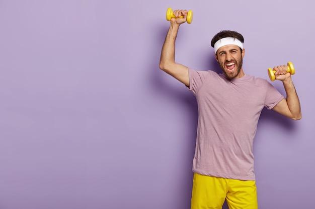 Un Sportif Motivé Entraîne Les Muscles, Soulève Des Haltères Jaunes, Porte Un Bandeau, Une Tenue Décontractée, Est Actif Photo gratuit