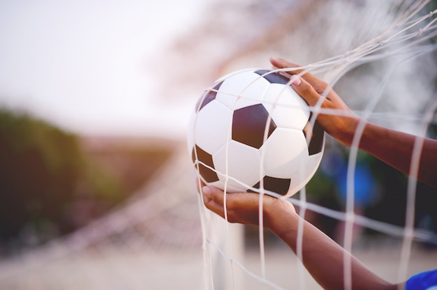 Les sportifs qui attrapent le ballon et le terrain de football. Photo Premium