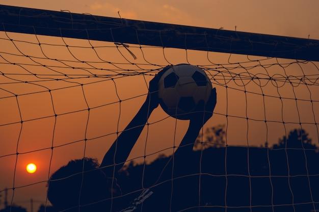 Les sportifs qui attrapent le ballon et le terrain de football. Photo Premium