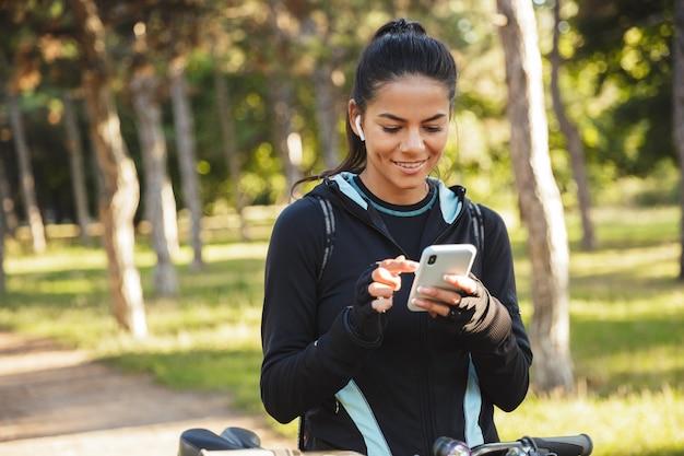 Sportive Ajustement Attrayant Avec Un Vélo Dans Le Parc, écoutant De La Musique Avec Des écouteurs Sans Fil, En Utilisant Un Téléphone Mobile Photo Premium