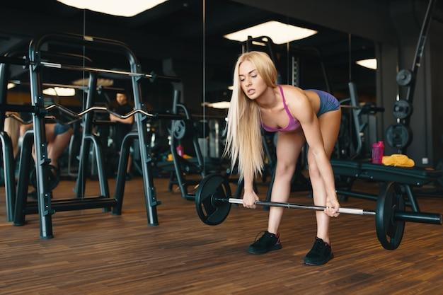 Sportive Blonde En Mini Short Soulevant Des Haltères à L'entraînement De Gym Photo gratuit