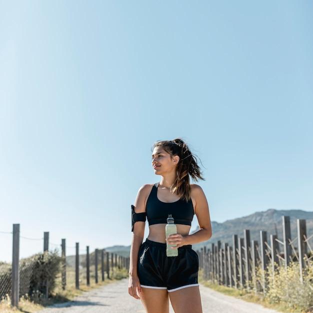 Sportive femme debout sur la route avec une bouteille d'eau Photo gratuit