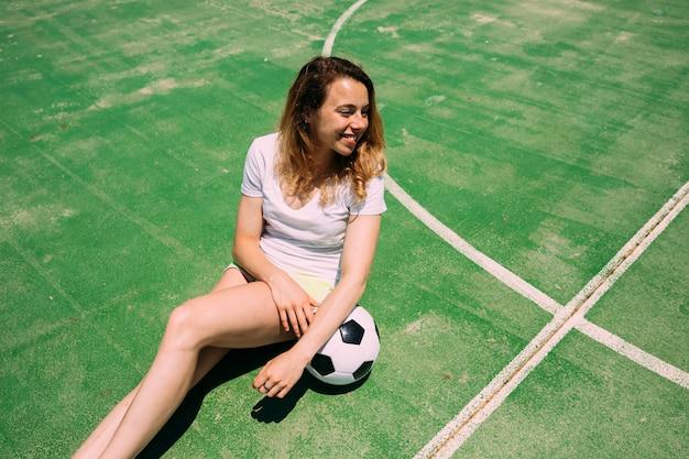 Sportive jeune femme assise avec ballon de foot Photo gratuit