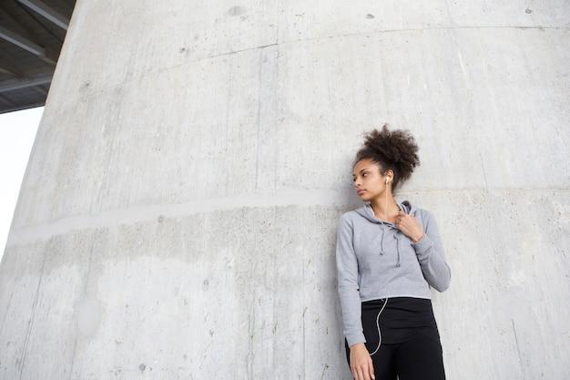 Sportive Jeune Femme Debout à L'extérieur Avec Des écouteurs Photo Premium