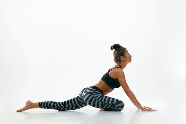 Sportive Jeune Femme Faisant La Pratique Du Yoga Isolé Sur Un Espace Blanc. Fit Modèle Féminin Flexible Pratiquant Photo gratuit