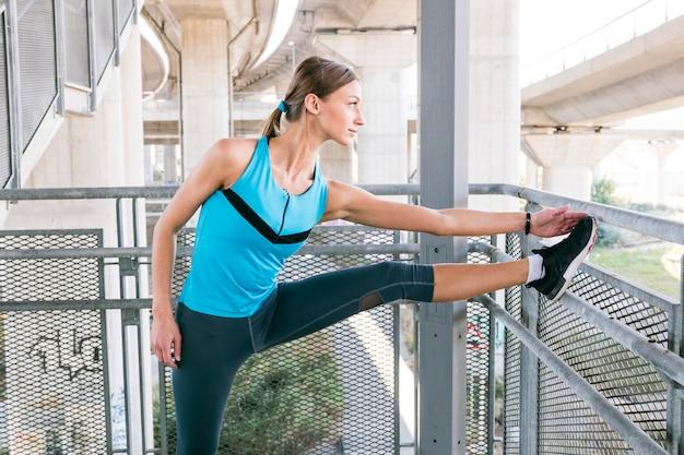 Sportive jeune femme s'étire avant de faire du jogging Photo gratuit