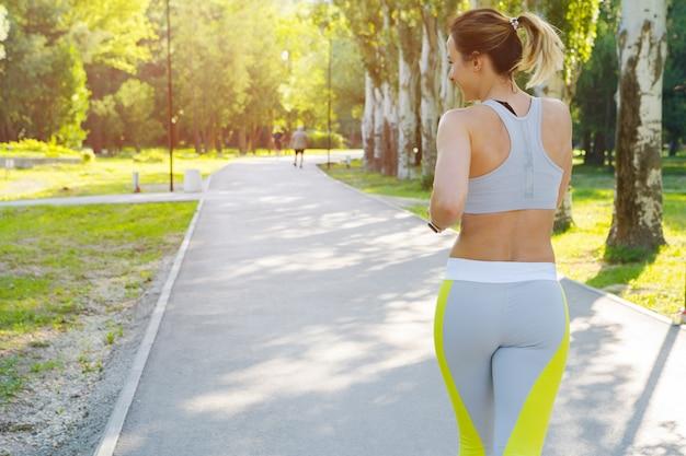Sportive jeune femme en tenue de sport en cours d'exécution dans le parc le matin Photo Premium
