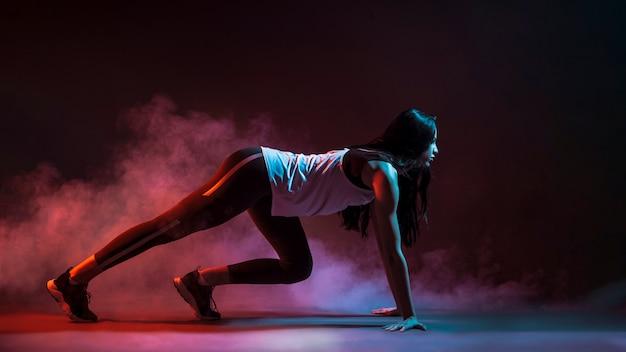 La sportive en position accroupie commence dans l'obscurité Photo gratuit