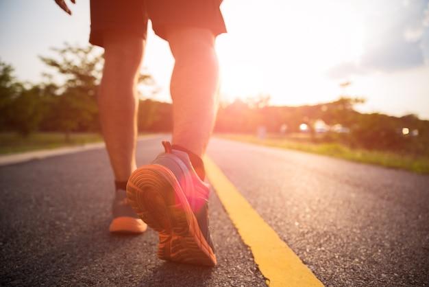 Sports un homme jambes en courant et marchant pendant le coucher du soleil. Photo Premium